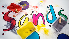 Coloured sands. In a sand art activity. The word sand is written on the table. Photo taken on March 2nd, 2015 Stock Image
