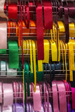 Coloured satin ribbons. A rack of coloured satin ribbons stock photos