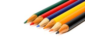 Coloured small pencils in colours green, red, blue, yellow, orange and black isolated on a seamless white background. Coloured small pencils in colours green Royalty Free Stock Image