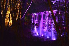 Illuminated Bridge and Waterfall. Coloured spotlights illuminate a japanese style bridge and waterfall at night Stock Image