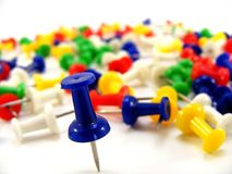 Coloured thumbtacks with DOF. A close up of a blue thumbtack with a faded background of other thumbtacks. Shallow DOF Royalty Free Stock Photos