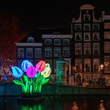 Coloured tulips of light float on a canal during the Festival of. Amsterdam, Netherlands – January 5, 2017: Coloured tulips of light float on a canal royalty free stock photo