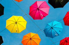 Coloured umbrellas hanging out of blue sky Royalty Free Stock Images