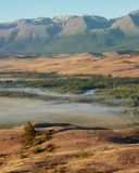 Coloured valley and bend of river with morning fog. Coloured valley and bend of river Chuya with morning fog on the background North-Chuya ridge in the dauwn stock images