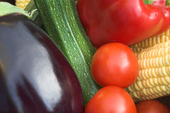 Coloured Veg. Brightly coloured summer vegetables including egg-plant, corn & tomatoes Stock Image