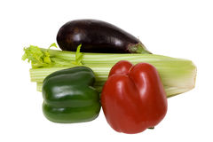 Coloured vegetables. Red & green peppers with an aubergine and a bunch of celery Royalty Free Stock Image