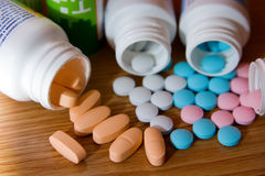 Coloured Vitamins. Closeup pink, white, blue and orange vitamins with bottles Stock Images