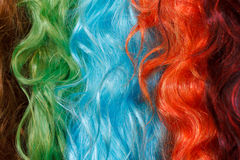 Coloured wigs with long wavy fake hair. Hanging next to each other Royalty Free Stock Photo