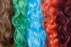 Coloured wigs with long wavy fake hair. Hanging next to each other royalty free stock photography