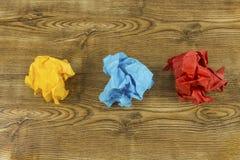 Coloured zerknitterte Papierbälle auf Holz Kreativitätskrisenkonzept Satz zerknitterte gelbe, blaue und rote Papierbälle Lizenzfreie Stockfotos