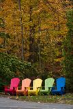 Colourful Adirondack aka Muskoka Chairs in Autumn stock images