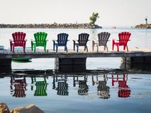 Adirondack Chairs by the Lake. Colourful Adirondack Chairs on the deck by the Lake Royalty Free Stock Images