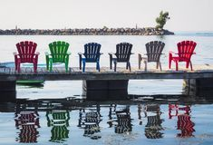 Adirondack Chairs by the water. Colourful Adirondack Chairs on the deck by the water Royalty Free Stock Photography