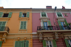 Colourful apartment buildings in Monaco. Brightly painted buildings with green shutters and iron railings royalty free stock images