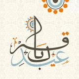 Colourful Arabic calligraphy text for Eid-Al-Adha celebration. Royalty Free Stock Image