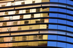 Colourful Architectual Reflections. Abstract architectural background. A modern glass structure with reflections of a warm coloured building and clear blue sky Royalty Free Stock Photography