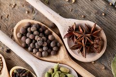 Spoons with aromatic various spices for cooking on old wooden board, close-up, flat lay, selective focus. stock image