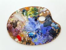 Colourful artists palette. Colourful artists oil paint palette on plain background stock photography