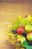Colourful autumn leaves, apples and pinecones on a wooden surface background. Stock Photos