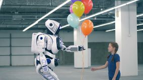 Colourful balloons are being gifted by a cyborg to a girl. 4K stock video