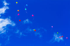 Colourful balloons high in the sky. Some colored balloons flying very high in a spring bllue sky Stock Photo