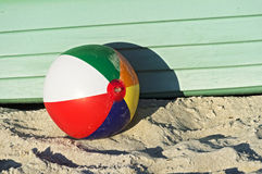 Colourful beach-ball in front of a green boat Royalty Free Stock Image