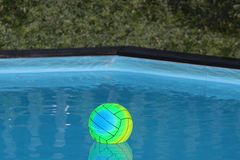 Colourful beach ball in a swimming pool stock images