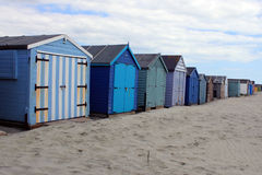 Colourful beach huts on beach Stock Images