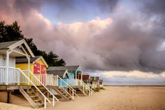Colourful beach huts on golden sand coast. Elevated colorful beach huts in stunning colours on a sandy North Norfolk coast. Sunrise clouds with an early morning Stock Image
