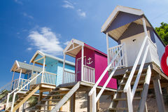 Colourful Beach Huts. Rows of colourful, wooden beach huts that are elevated on stilts and accessed by steps on a sandy beach and under a blue sky with summer Stock Images