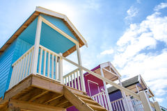 Colourful Beach Huts. Rows of colourful, wooden beach huts that are elevated on stilts and accessed by steps on a sandy beach and under a blue sky with summer Royalty Free Stock Images