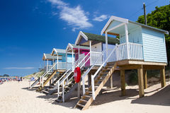 Colourful Beach Huts. Rows of colourful, wooden beach huts that are elevated on stilts and accessed by steps on a sandy beach and under a blue sky with summer Stock Photos