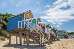 Colourful Beach Huts. Rows of colourful, wooden beach huts that are elevated on stilts and accessed by steps on a sandy beach and under a blue sky with summer Royalty Free Stock Photography