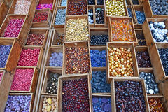 Colourful beads in different sizes and shapes sold in wooden compartment. In a flea market shop in Paris France royalty free stock photo