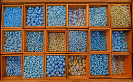 Colourful beads in different sizes and shapes sold in wooden compartment. Colourful beads mainly blue in various tones in different sizes and shapes sold in stock photos