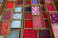 Colourful beads in different sizes and shapes sold in wooden compartment Royalty Free Stock Photos