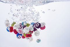 Colourful beads falling into water. Colourful beads falling into clean pure water creating motion air bubbles and surface turbulence in the liquid royalty free stock images