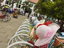 Colourful bicycles and hats for hire. JAKARTA, NOV 14, 2010:  Colourful bicycles and hats for hire in a public square in Jakarta, Indonesia on November 14, 2010 Stock Photography