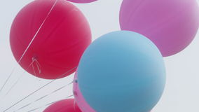 Colourful big balloons flying in the air with clear sky closeup stock footage