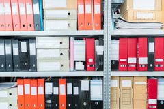 Colourful blank blind folders with files in the shelf. Archival, stacks of documents at the office or library. Physical document royalty free stock photo