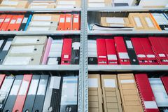 Colourful blank blind folders with files in the shelf. Archival, stacks of documents at the office or library. Physical document stock image