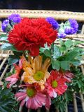 Colourful blooming flowers basket. Red Carnation and fancy colour Gerbera with green leaves in bamboo basket brighten the day with best wishes royalty free stock photos
