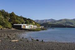 Colourful boat sheds on stony shoreline. Colourful boat houses along the stony shore of Duvauchelle Bay, Akaroa Harbour, Banks Peninsula, New Zealand Royalty Free Stock Image