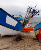 Colourful boats on beach. Some colourful fishing boats standing on a beach, winter weather, some buoy flag posts Royalty Free Stock Photo