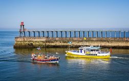 Colourful boats crossing on way in to Whitby harbour royalty free stock image