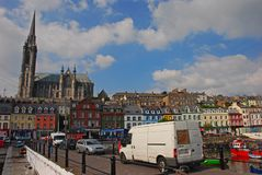 Saint Colman Cathedral and the iconic traditional waterfront shophouses at Cobh, Republic of Ireland royalty free stock photography