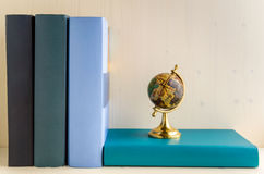 Colourful Books and Wooden Background. Books and a Small Globe on a Wooden Shelf stock image