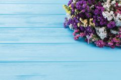 Colourful boquet of limonium flowers on blue wooden table. royalty free stock photos