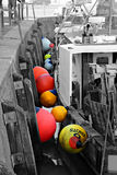 Colourful buoys in whitstable harbour. Black and white photo of fishing boats moored in whitstable harbour with colour popped buoys Stock Photo