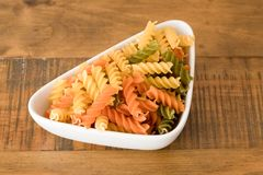 Bowl of Coloured Pasta Twirls. A colourful bowl of pasta twirls on a wooden oak table Royalty Free Stock Photography